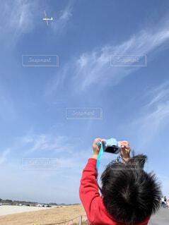 空を見上げてカメラをかまえる子どもの写真・画像素材[4538256]