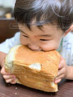 小さな男の子がパンを食べているの写真・画像素材[3470835]