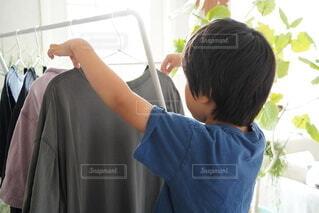 部屋干しを手伝っている男の子の写真・画像素材[4671331]