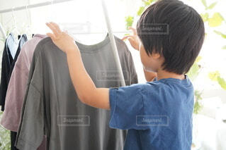 部屋干しを手伝っている男の子の写真・画像素材[4671332]