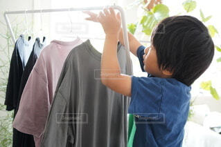 部屋干しを手伝っている男の子の写真・画像素材[4671330]