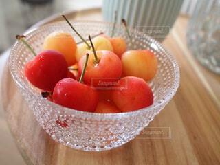 木製のテーブルの上に座っている果物のボウルの写真・画像素材[4744623]