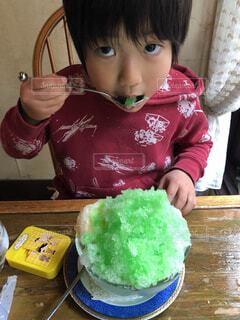 食べ物を食べるテーブルに座っている小さな女の子の写真・画像素材[4744731]