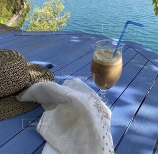 湖畔のテーブル湖畔でひと息。麦わら帽子を置いてアイスコーヒーをいただきます。の写真・画像素材[4759936]