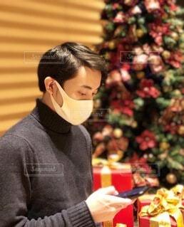 クリスマスツリーの前でスマホ片手に恋人を待つマスク姿の男性の写真・画像素材[4006434]