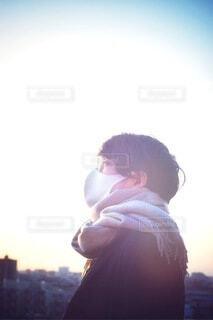 夕陽を眺めるメガネをかけたマスク姿の男性の写真・画像素材[4148877]
