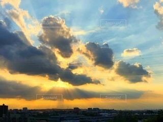 幻想的な日没時の太陽光線が雲の合間から都市の上空に差し込むの写真・画像素材[4839796]