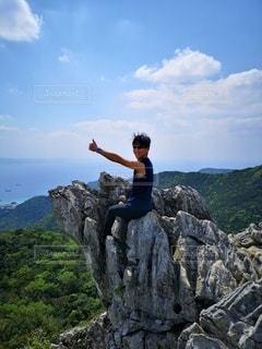 大きな岩の前に立っている男の写真・画像素材[3580151]