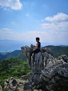 岩の丘の上に立っている人の写真・画像素材[3580150]