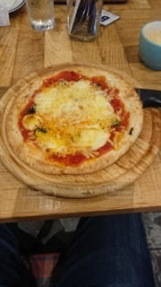 木製のまな板の上に座っているピザの写真・画像素材[3530464]