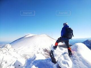 雪に覆われた山の上に乗っている人の写真・画像素材[3588376]