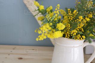 テーブルの上に花瓶に黄色い花の写真・画像素材[1837955]