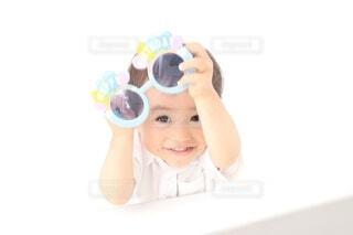 サングラスを掲げる男の子の写真・画像素材[3616730]