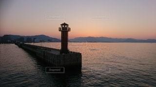 夕焼けに染まる桟橋灯台の写真・画像素材[3611963]