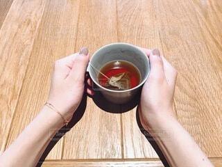 木製のテーブルの上でコーヒーを一杯持っている女性の写真・画像素材[3669468]