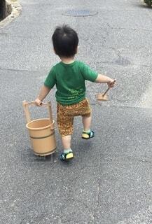 子ども,屋外,道路,手持ち,人物,人,手桶,地面,ポートレート,少年,柄杓,ライフスタイル,手元,男の子の後ろ姿