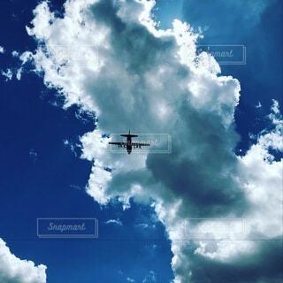 曇った青空を飛んでいる飛行機の写真・画像素材[3627902]