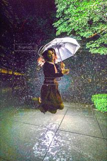 雨の中で黄色い傘を持っている人の写真・画像素材[845455]