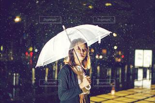 傘を持って雨の中で立っている女性の写真・画像素材[845456]