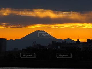 背景に都市がある水域に沈む夕日の写真・画像素材[3794091]