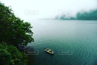 水の体の隣に川に沿って浮かぶボートの写真・画像素材[3640171]