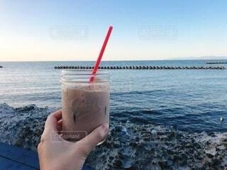 カフェ,海,空,夏,カメラ,屋外,ジュース,ビーチ,テラス,水面,海岸,手持ち,人物,写真,ポートレート,ドリンク,ライフスタイル,手元,ソフトド リンク