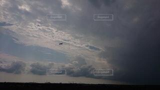 曇り空に飛行機の影の写真・画像素材[3686174]