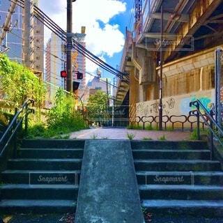 階段と落書きと高架線路と街並と緑と踏み切りの写真・画像素材[3664590]