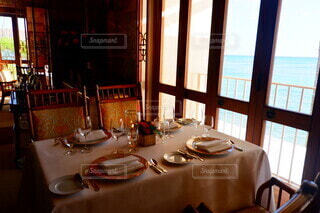 窓の前にダイニングルームのテーブルの写真・画像素材[3688890]