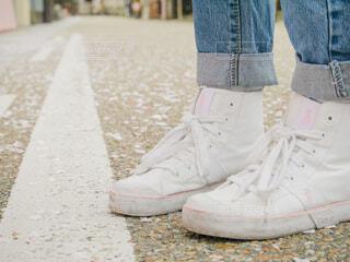 桜の花びらが散る道で白いスニーカーのクローズアップの写真・画像素材[4300698]