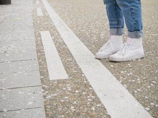桜の花びらが散る道路で立つ白いスニーカーとデニムを履いた女の子の写真・画像素材[4300700]
