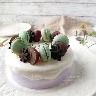 白いお皿と、マカロンとぶどうのデコレーションケーキの写真・画像素材[3703496]