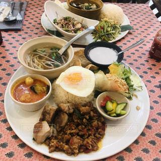 テーブルの上に置かれた料理の載った皿の写真・画像素材[3932257]