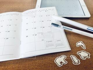 テーブルの上に置かれたスケジュール帳とタブレットの写真・画像素材[4006757]