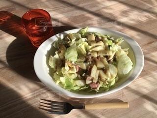 テーブルの上にレタスきのこサラダ皿の写真・画像素材[3893823]