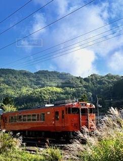 秋晴れの日に山の近くで列車の線路を移動する列車の写真・画像素材[3800795]