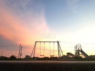 夕陽に架かるブランコの写真・画像素材[3707577]