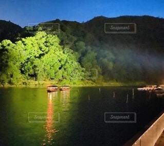 水の体の隣に川に沿って浮かぶボートの写真・画像素材[3711899]