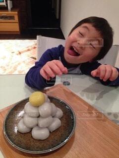 テーブルの団子を欲しがる男の子の写真・画像素材[4110854]