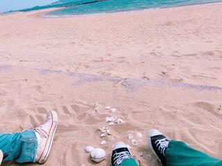 砂浜で座って話をしている2人のスニーカーの写真・画像素材[4330510]