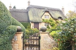コッツウォルズを背景にしたレンガ造りの建物の前の庭の写真・画像素材[3758608]