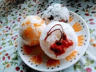 皿の上の食べ物は。丸いオニギリの写真・画像素材[3745755]