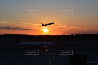 日没時に空を飛んでいる飛行機の写真・画像素材[3750933]