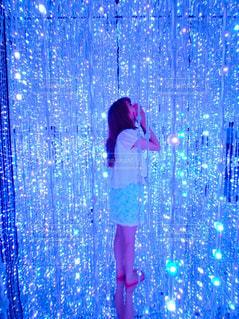 カーテンの前に立っている女性の写真・画像素材[770367]