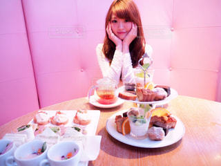食品のプレートをテーブルに座っている女性の写真・画像素材[852302]