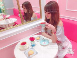 小さな女の子のテーブルに座っての写真・画像素材[870222]