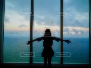 窓から飛んで人の写真・画像素材[924622]
