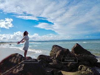 岩のビーチに立っている人の写真・画像素材[925561]