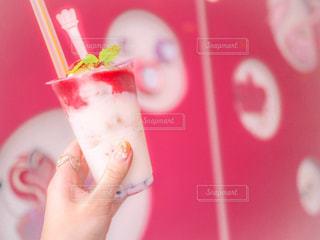 赤のカップを持っている手の写真・画像素材[928125]