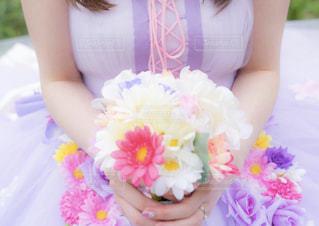 彼女は手に花とテーブルに座っている女性 - No.935665